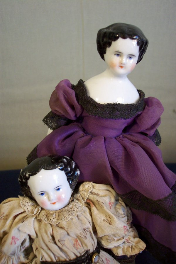 17: Two china head dolls, both 8 inch, doll in purple d