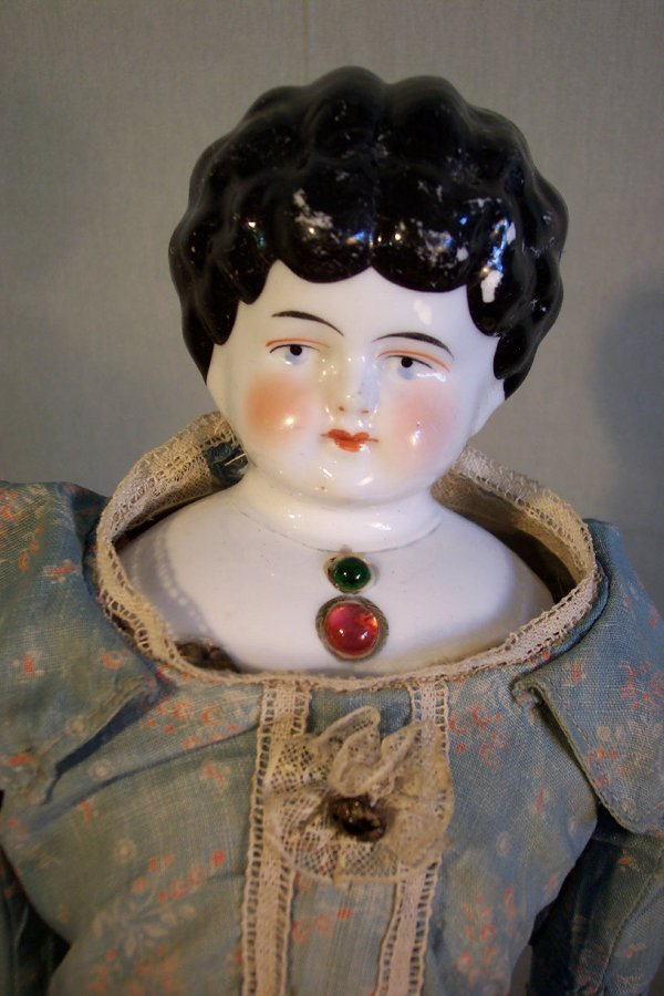 20: China head doll, 18 inch, jeweled bust, leather bod