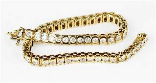 A Diamond and 14 Karat Yellow Gold Line Bracelet.