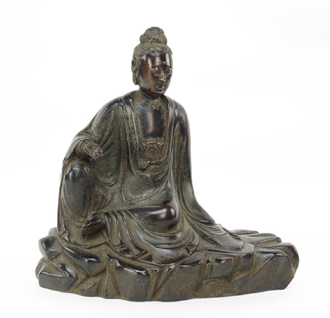 A Chinese Patinated Bronze Figure of a Seated Guan Yin.
