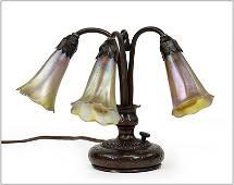 A Tiffany Studios Three-Light Lily Piano Lamp.