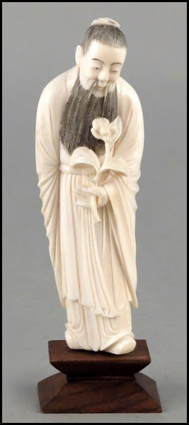 1143007: CARVED IVORY FIGURE HOLDING A FLOWER.