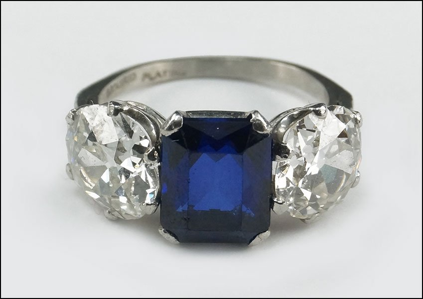 A PLATINUM, DIAMOND, AND SYNTHETIC SAPPHIRE RING.