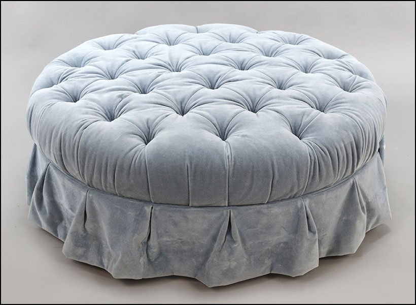 AN UPHOLSTERED TUFTED OTTOMAN.