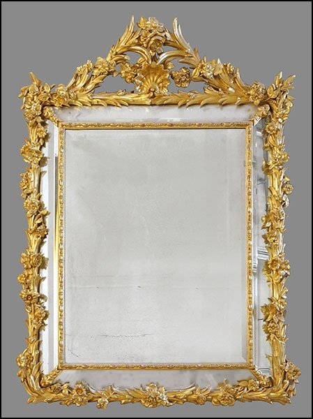 A French Rococo Style Carved Giltwood Mirror.