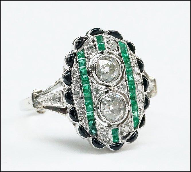 An Art Deco Platinum, Diamond, and Emerald Ring.