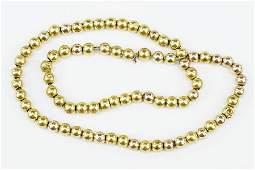 A 14 Karat Yellow Gold Bead Necklace.