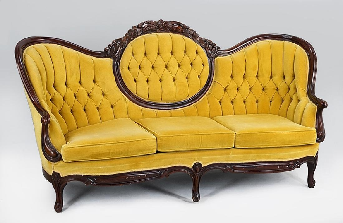 A Victorian Style Carved Walnut Sofa.
