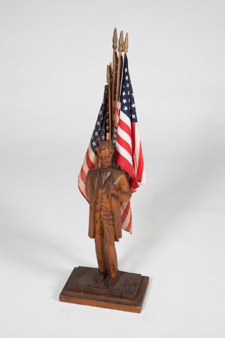 FOLK ART CARVING OF ABRAHAM LINCOLN before FLAGS