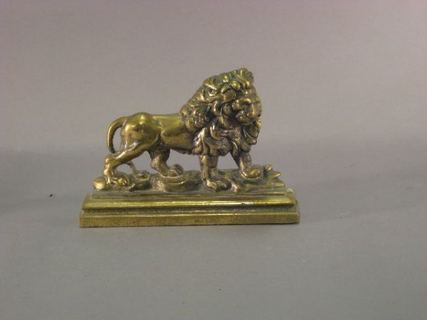 270: Figural brass door stop of lion on a rock formatio