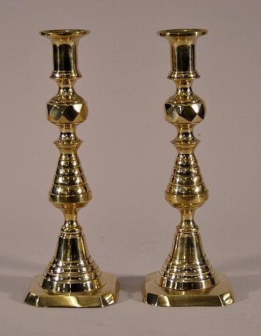 11: Pair of early brass bee hive push up candlesticks.
