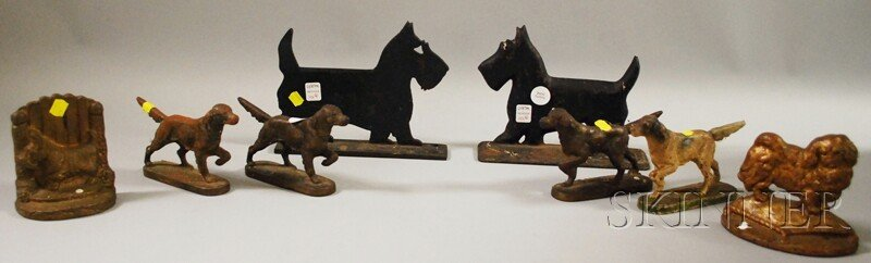 1101: Four Cast Iron Dog Figural Doorstops, a Bookend,