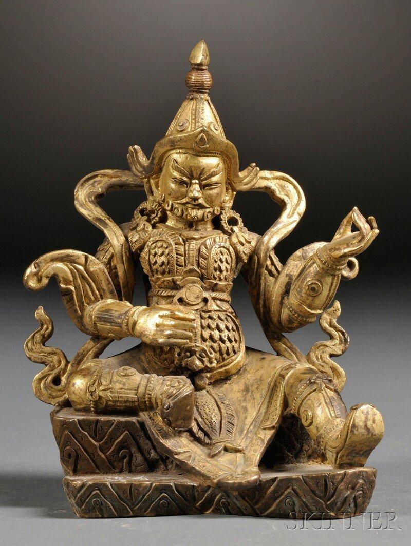Gilt-bronze Buddha, China, wearing a helmet, earrings,
