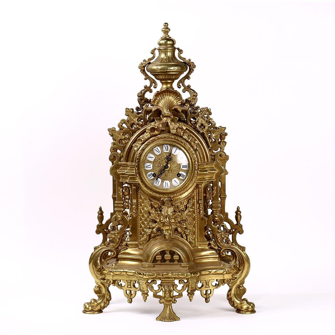 Rococo Revival style brass mantle clock, the round face