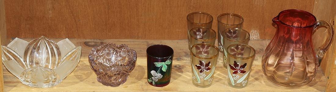 One shelf of glassware including a cranberry glass