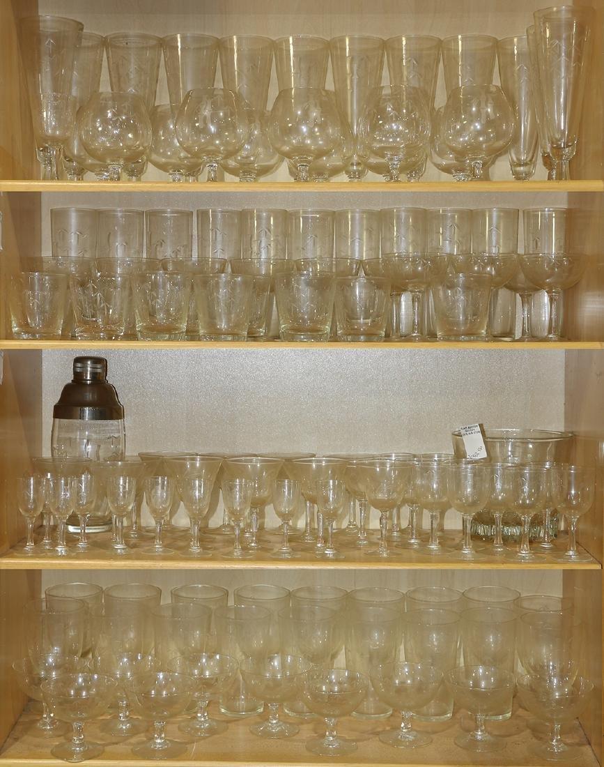 Five shelves of etched glass stemware, including beer,