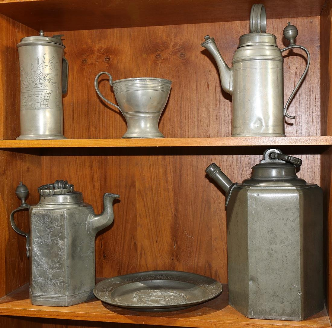 Two shelves of pewter table articles