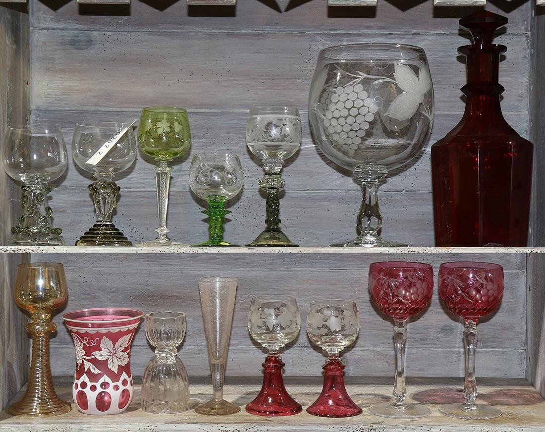 Two shelves of wine themed glassware in associated