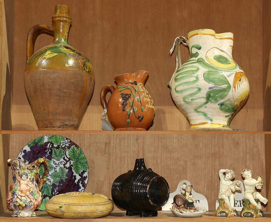 Two shelves of decorative art relating to wine,