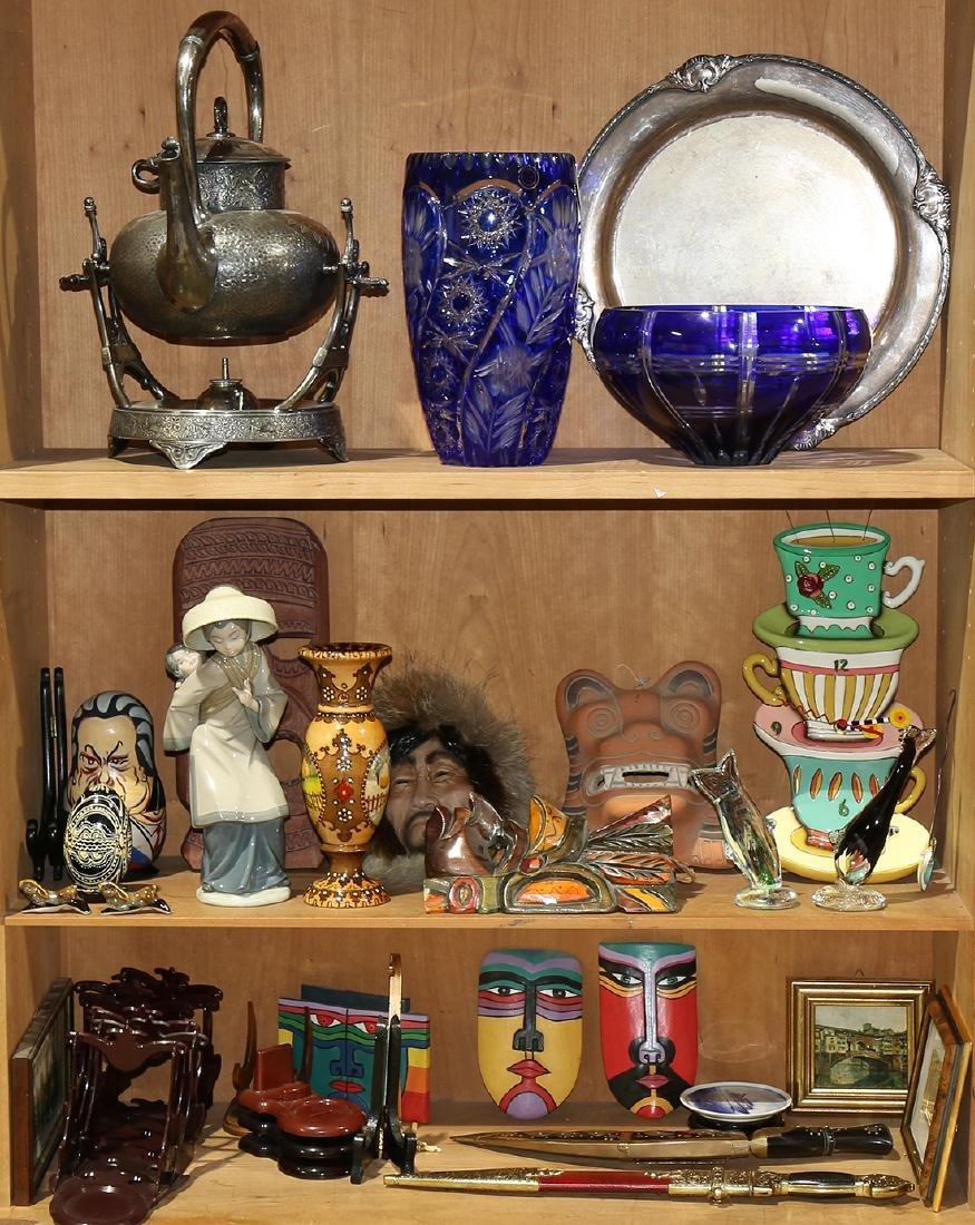 Three shelves of decorative art including a silver
