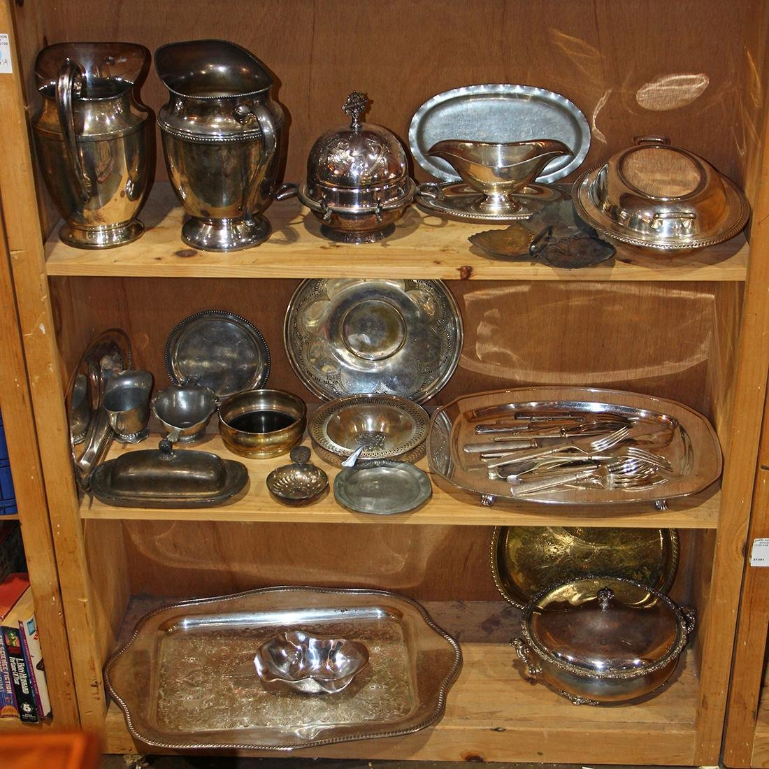 Three shelves of silver plate table articles