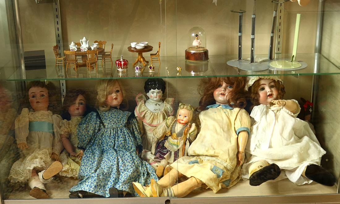 Two shelves of dolls and doll house furniture