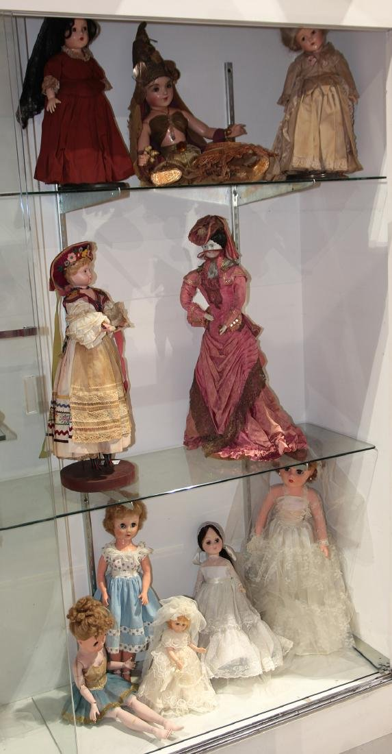 Three shelves of composition and porcelain dolls