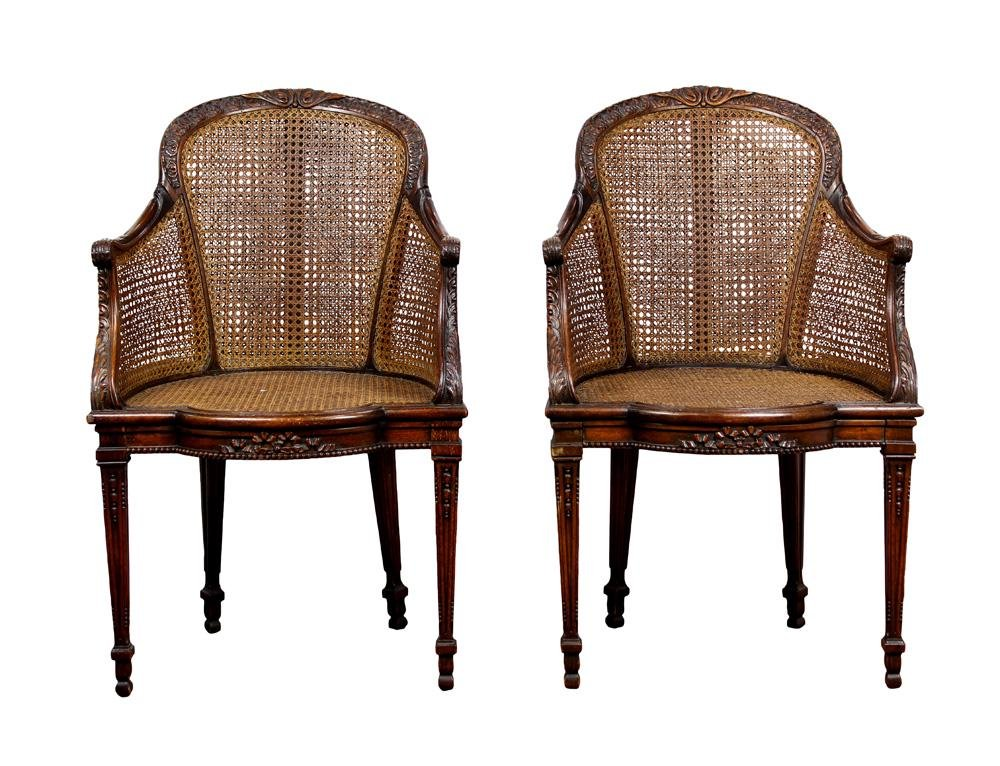 A pair of Louis XV style caned walnut bergeres