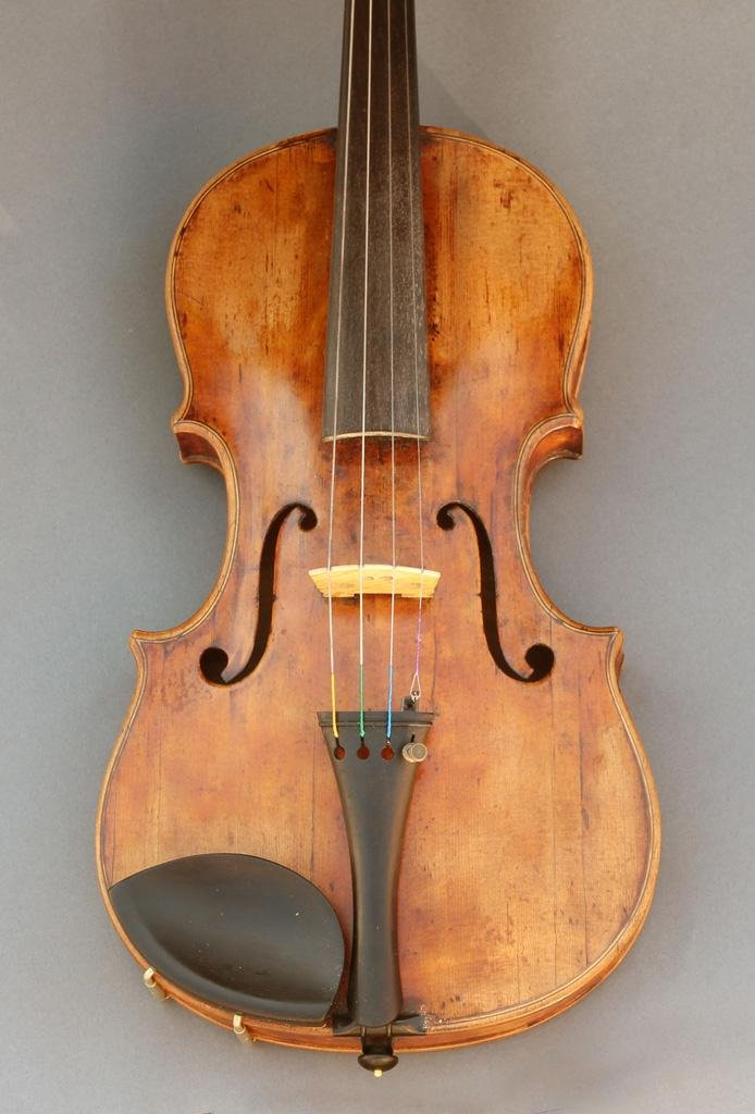An antique violin, having a maple body with spruce top,