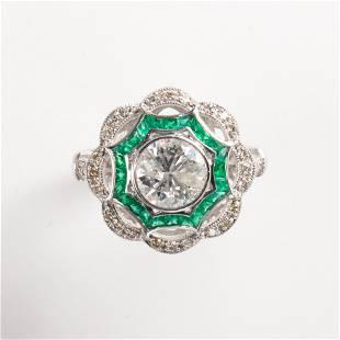 A diamond, emerald and platinum ring