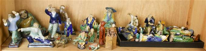 A shelf of mostly Chinese Shiwan figures