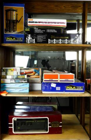 Three shelves of model trains in boxes