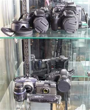 (lot of 7) (2) Olympus cameras, an Olympus lens, (3)