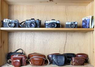 Two shelves of vintage cameras including a Yashica GSN