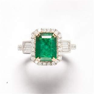 An emerald, diamond and fourteen karat white gold ring