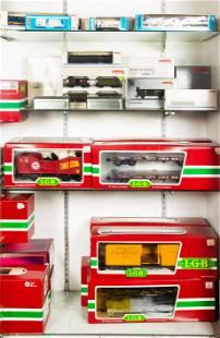 Four shelves of boxed model trains, including Marklin