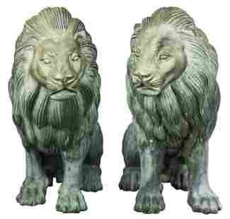 A pair of patinated metal outdoor lion sculptures