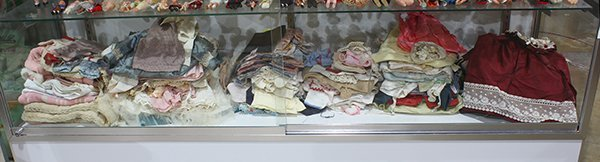 One shelf of doll clothes inlcuding period linen and