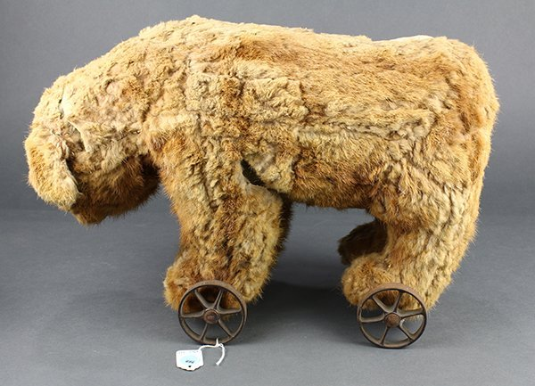 Vintage Steiff fur teddy bear mounted to iron wheels,