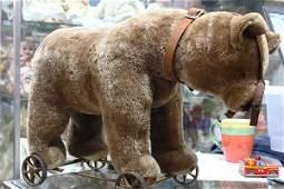 Early Steiff mohair bear on wheels, wearing a brown