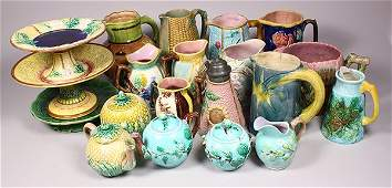 Three shelves of majolica table articles, including