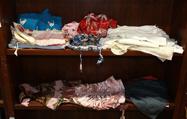 Two shelves of doll clothes, many with lace accents,