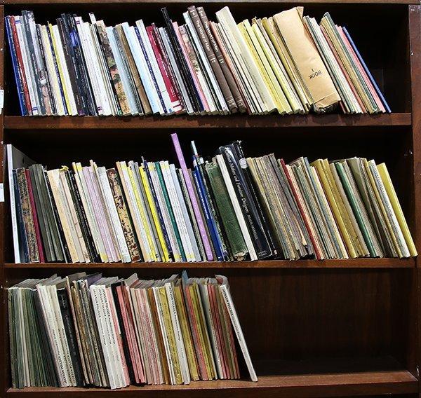 Three shelves of auction catalogs including
