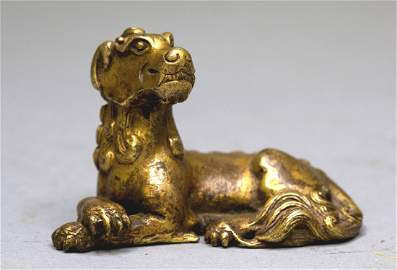 A SMALL GILT-BRONZE MYTHICAL BEAST