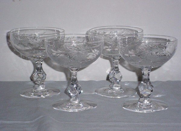 4: Four colorless etched crystal champagne glasses.