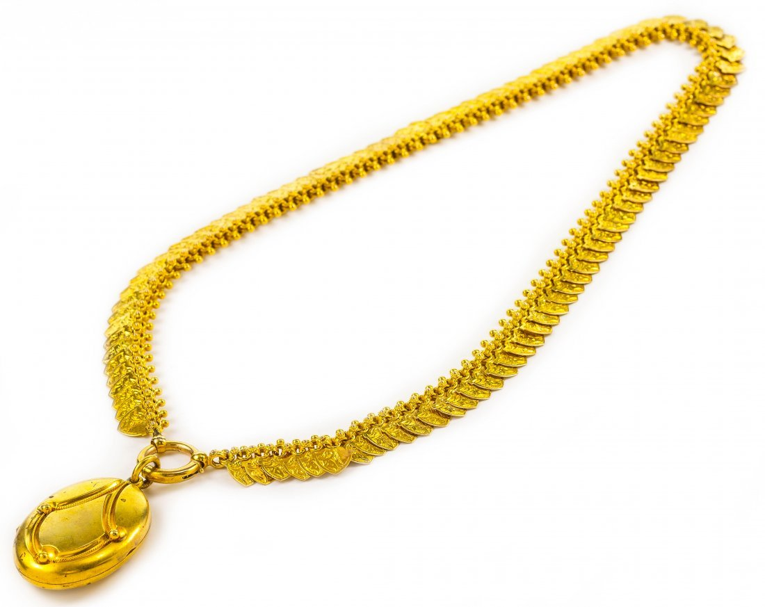 AN ANTIQUE GOLD NECKLACE WITH A GOLD LOCKET PENDANT