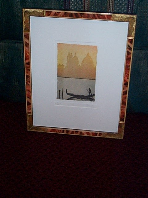 13: Framed wood block depicting a man in a boat with a