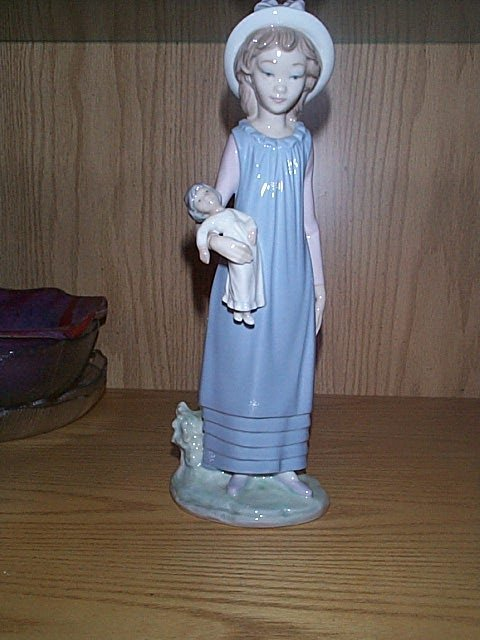 13: Lladro figurine, depicting a girl holding a doll.
