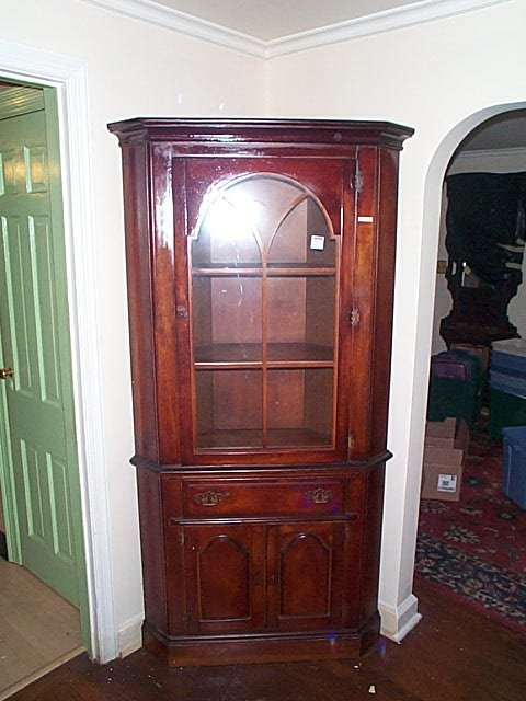 966: Cherry corner cabinet. Local delivery available wi