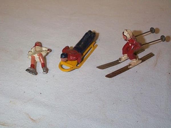 24: Lot of (3) Lead figurines including skier, sleder,